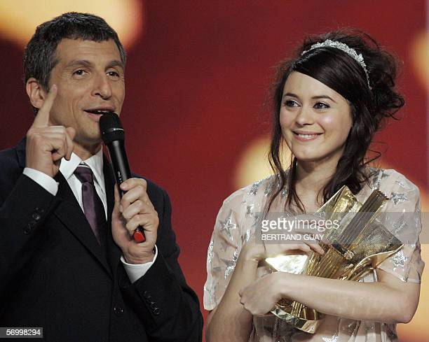 "French singer Emilie Simon receives an award for best soundtrack of the year from TV host Nagui during the 21st ""Victoires de la musique"" ceremony ,..."
