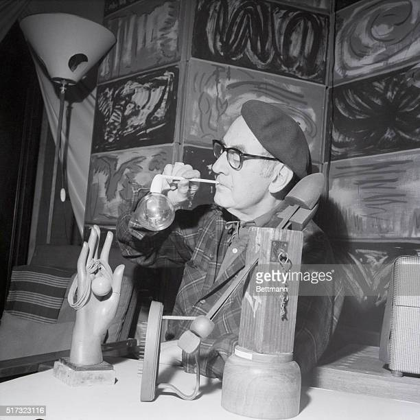 5/20/1964 Paris France From 'Dada' to 'Pop' Surrounded by his objets d'art Man Ray seemingly blows a soap bubble from a slender white pipe but...