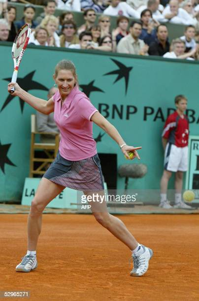 German Steffi Graf returns the ball to Belgium Justine HeninHardenne and French Gilles Simon during their friendly double mixed tennis match on the...