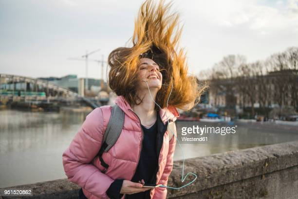 Paris, France, happy young woman listening music with earphones and smartphone tossing her hair
