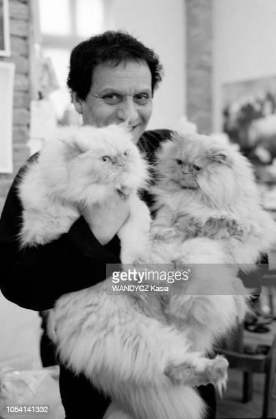 le couturier Azzedine ALAIA dans son atelier portant ses deux chats persans dans les bras