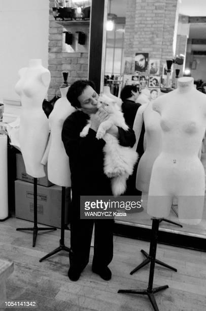 Paris France Le couturier Azzedine ALAIA dans son atelier Ici en pied embrassant son chat persan qu'il tient dans ses bras au milieu de mannequins de...