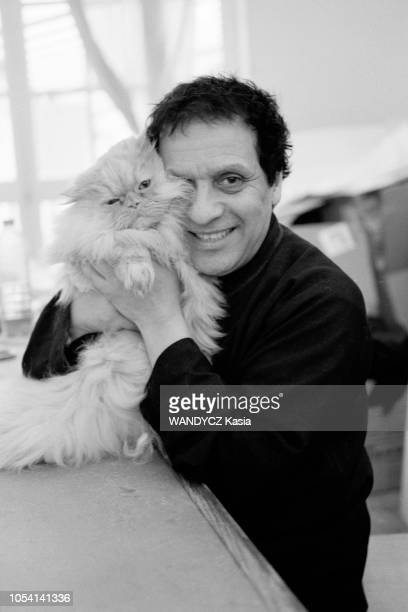 Paris France Le couturier Azzedine ALAIA dans son atelier Ici souriant et faisant un câlin à l'un de ses chats persans