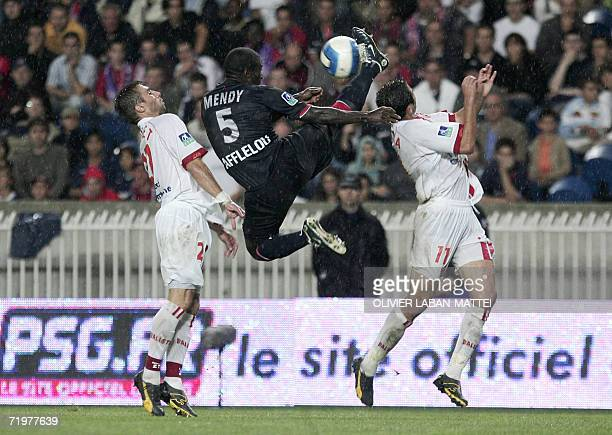 Paris SaintGermain defender Bernard Mendy jumps to kick the ball next to Nancy's defender David Sauget and Nancy's forward Monsef Zerka during the...