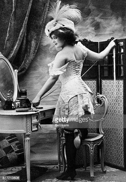 Photo of a woman tying her corset while standing in front of a mirror. Ca. 1890-1900.