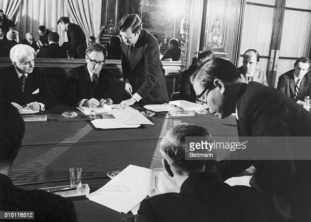 1/23/1973 Paris France Photo released by the White House 1/24 shows Dr Henry Kissiinger background center initialling the cease fire agreement in...