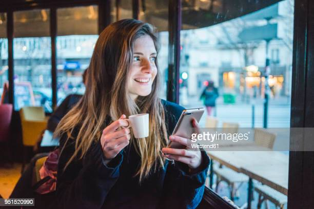 Paris, France, portrait of smiling young woman with smartphone drinking espresso in a coffee shop