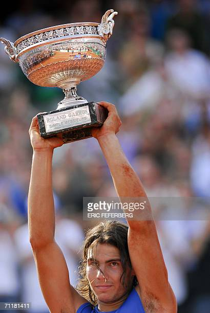 Spain's Rafael Nadal holds the trophy after defeating Swiss Roger Federer during the French tennis Open finals at Roland Garros in Paris 11 June 2006...