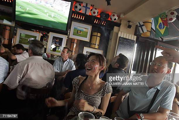 Supporters of the French national football team react as they watch on a TV screen the 2006 soccer World Cup match opposing France to Switzerland 13...
