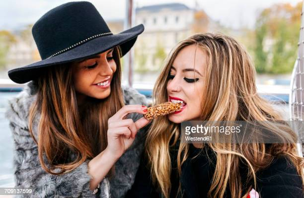 Paris, France, two tourists taking a cruise on Seine River eating a snack