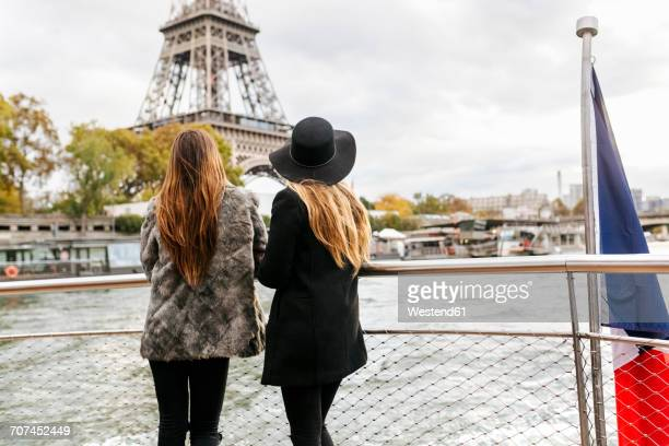 paris, france, two tourists taking a cruise on seine river with eiffel tower in the background - passagier wasserfahrzeug stock-fotos und bilder