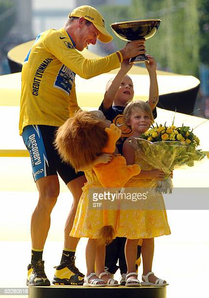US Lance Armstrong celebrates with his three children on the winners' podium after the 21st stage of the 92nd Tour de France cycling race between...