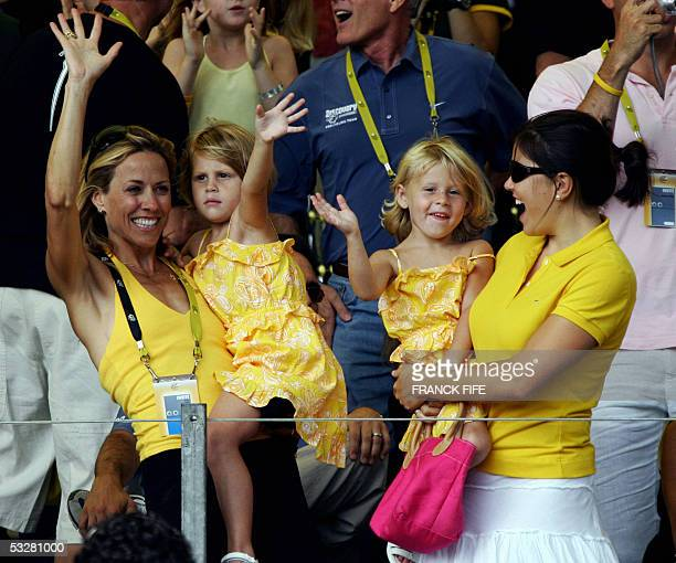 US Lance Armstrong's girlfriend US pop singer Sheryl Crow his two daughters and an unidentified nanny cheer in the stands on the Champs Elysees the...