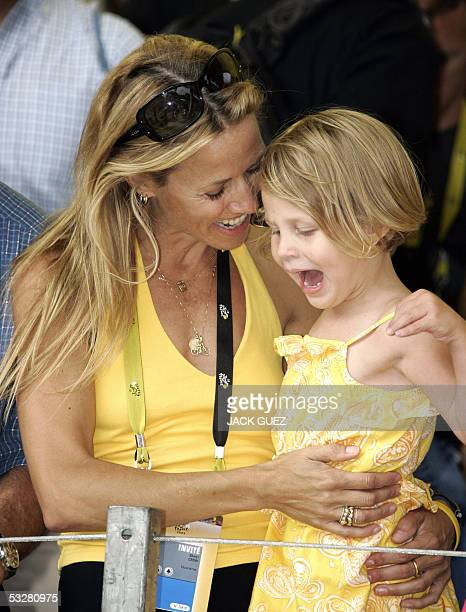 US pop singer and girlfriend of US Lance Armstrong Sheryl Crow jokes with one of his twins in the stands on the Champs Elysees during the final stage...