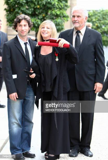 US singer Barbra Streisand poses with her husband James Brolin and her son Jason as she leaves the Elysee Palace after being awarded by French...