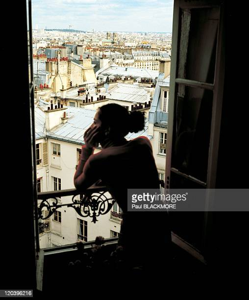 Paris France Woman watching Parisian roofs from her apartment in Montmartre