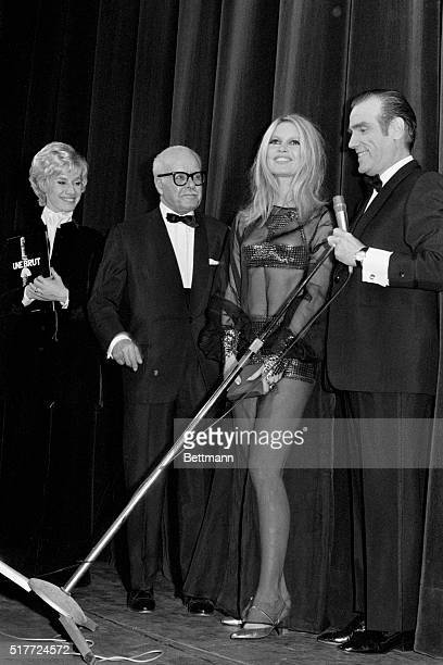 French film star Brigitte Bardot wearing a long transparent dark gown with a bodice over a silvery microskirt receives the award Queen of the Night...