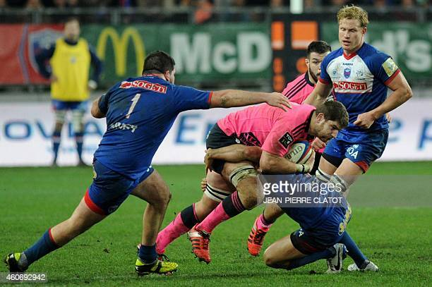 Paris' French lock Pascal Pape is tackled during the French Top 14 rugby union match Grenoble vs Stade Français on December 19 2014 at the Stade des...