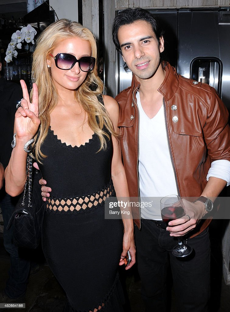 Paris Hilton (L) and actor Cesar D' La Torre attend the DT Model Management 2 Year Anniversary Celebration on July 24, 2014 at Pump in West Hollywood, California.