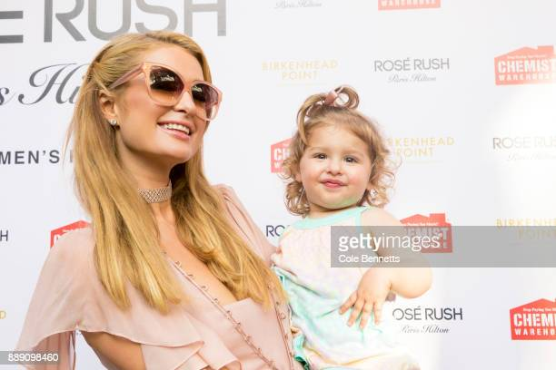 Paris Hilton holds a little girl for a photo during a promotion visit to Australia to launch her 23rd fragrance Rosé Rush on November 30 2017 in...