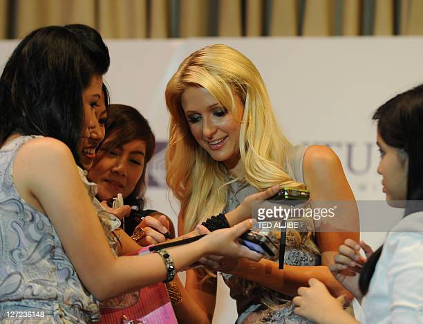 Paris Hilton of the US and hotel chain heiress signs autographs on the arm of one of her fans after a press conference in the financial district of...