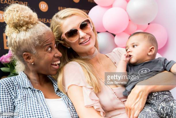 Paris Hilton poses for a photo holding a fans baby during a promotion visit to Australia to launch her 23rd fragrance Rosé Rush on November 30 2017...