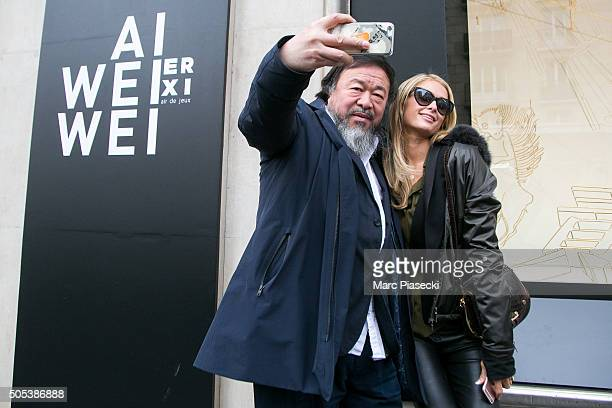 Paris Hilton poses for a selfie with artist Ai Wei Wei as they visit the 'Ai Wei Wei Er Xi' exhibition at Le Bon Marche department store on January...