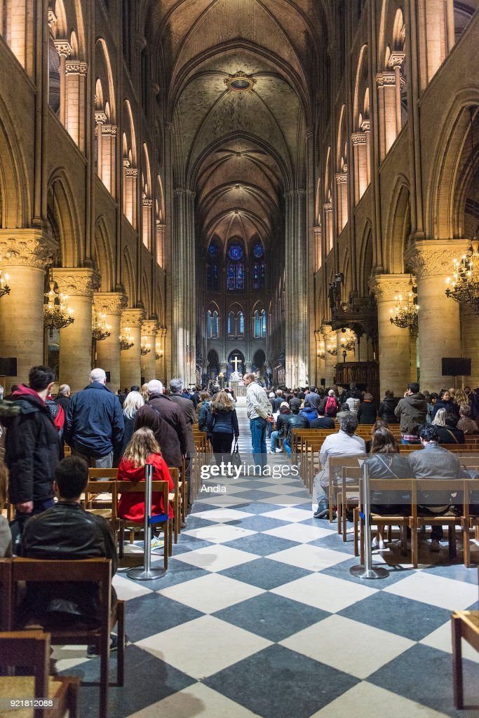 interior of Notre-Dame de Paris on the Ile de la Cite, in the 4th arrondissement (district). Believers attending a mass.
