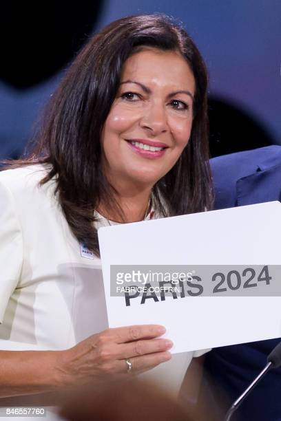 Paris Mayor Anne Hidalgo cries with the card bearing the name of Paris 2024 after the vote during the 131st IOC session in Lima on September 13 2017...