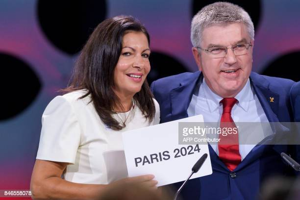 Paris Mayor Anne Hidalgo cries with the card bearing the name of Paris 2024 next to International Olympic Committee President Thomas Bach after the...