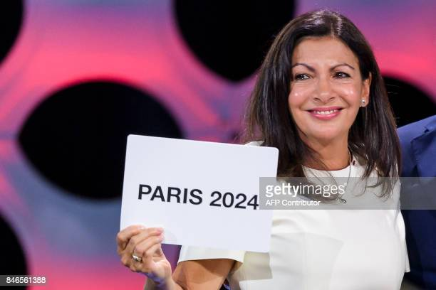 TOPSHOT Paris Mayor Anne Hidalgo gets emotional as she shows the card bearing the name of Paris 2024 after the vote during the 131st IOC session in...