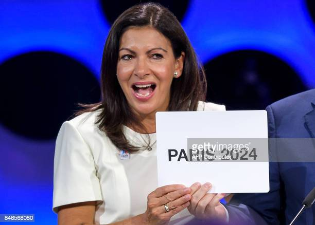 Paris Mayor Anne Hidalgo gets emotional as she shows the card bearing the name of Paris 2024 after the vote during the 131st IOC session in Lima on...
