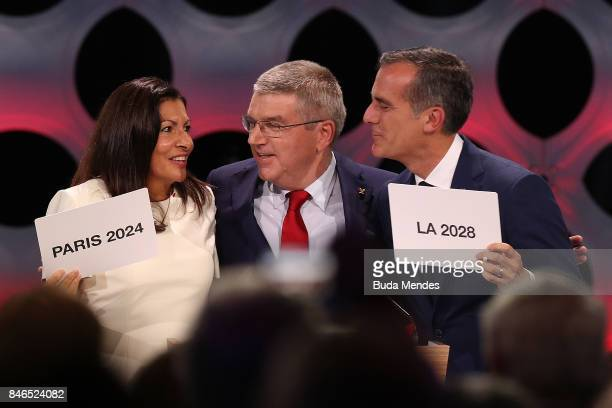 Paris Mayor Anne Hidalgo IOC President Thomas Bach and Los Angeles Mayor Eric Garcetti react after the confirmation of the tripartite agreement which...