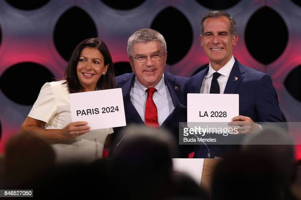 Paris Mayor Anne Hidalgo, IOC President Thomas Bach and Los Angeles Mayor Eric Garcetti react after the confirmation of the tripartite agreement...