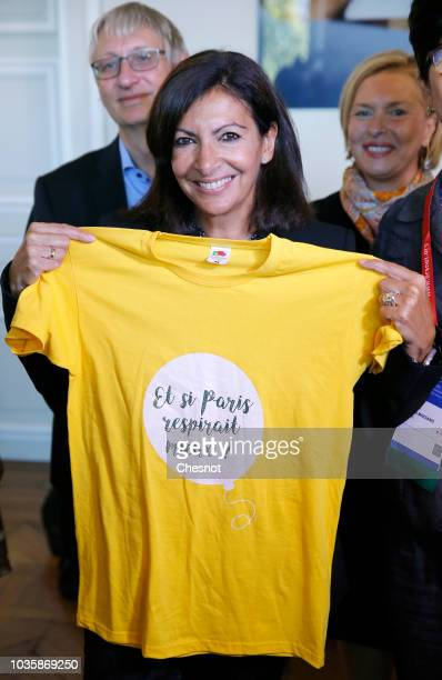 Paris Mayor Anne Hidalgo poses with a tee shirt with the words 'and if Paris breathed better' during the European Lung Foundation award ceremony on...