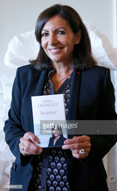 Paris Mayor Anne Hidalgo poses with her book 'Breathe' during the European Lung Foundation award ceremony on September 19 2018 in Paris France On...