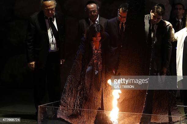 Paris Mayor Anne Hidalgo rekindles the eternal flame at the Hall of Remembrance during her visit on May 11 2015 to the Yad Vashem Holocaust Memorial...