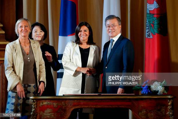Paris Mayor Anne Hidalgo shakes hands with South Korean President Moon Jaein next to his wife Kim Jungsook and French Minister for Disabled People...