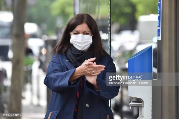 Paris Mayor Anne Hidalgo wearing a protective facemask rubs her hands as she inaugurates a public hydroalcoholic gel dispenser installed on a bus...