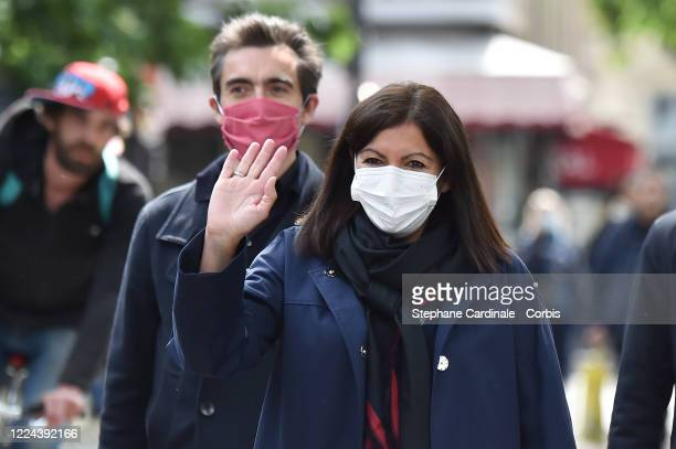 Paris Mayor Anne Hidalgo wearing a protective facemask salutes as she arrives to inaugurate a public hydroalcoholic gel dispenser installed on a bus...