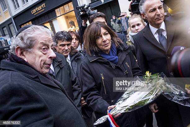 Paris Mayor in Paris Anne Hidalgo carries flowers as she arrives with columnist of French satirical newspaper Charlie Hebdo Patrick Pelloux and...