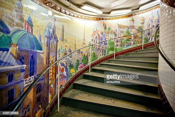 paris metro station abbesses: painted mural and spiral staircase - nun stock photos and pictures