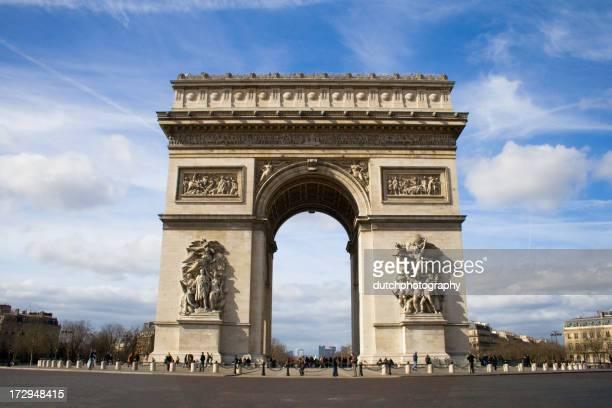 Paris Monument under a cloudy blue sky along a paved street