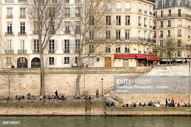 Paris on a nice day in spring. People enjoying the weather along Gaui de Bourbon.