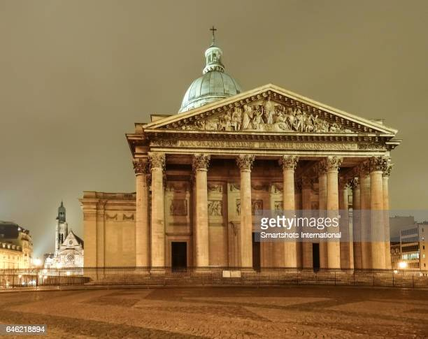 Paris Pantheon illuminated at night with church of Saint Etienne du Mont church on background, France