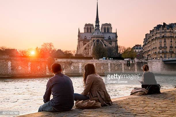 Paris, People resting along the Seine River at Sunset