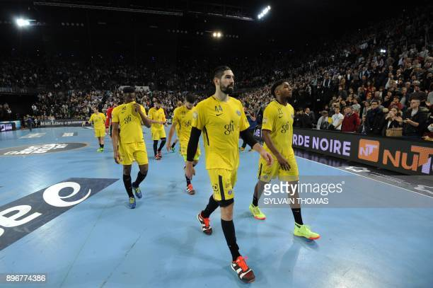 Paris' players leave the court after being defeated during the French D1 handball match between Montpellier and Paris at Sud de France Arena on...