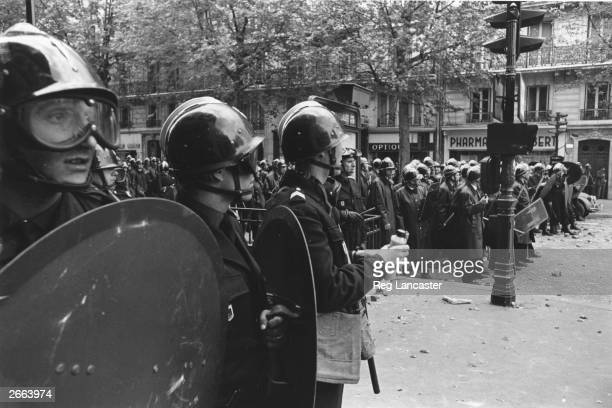 Paris police shelter behind riot shields during the student riots