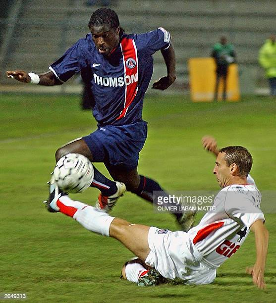 Paris Saint Germain's defender Bernard Mendy jumps to avoid the tackle of Ajaccio's midfielder David Terrier 25 October 2003 during their French L1...