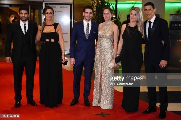 Paris Saint Germain's footballer Angel di Maria Boca Juniors' footballer Fernando Gago and Sevilla's footballer Ever Banegas pose with their wives...